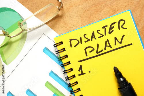Notepad with disaster plan on a wooden table. Fotobehang