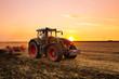 Leinwandbild Motiv Tractor on the barley field by sunset.