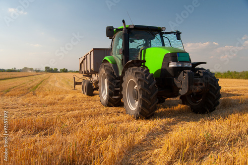 Foto  Modern green tractor on agricultural field during harvest on sunny summer day