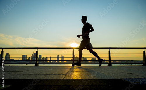 Silhouette of jogger running at sunset in front of the city skyline  - 92573965