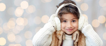 Happy Little Girl In Earmuffs Over Holidays Lights
