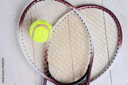 Heart shape made from tennis rackets. Close up on tennis racket and ball. Sport equipment background, wallpaper