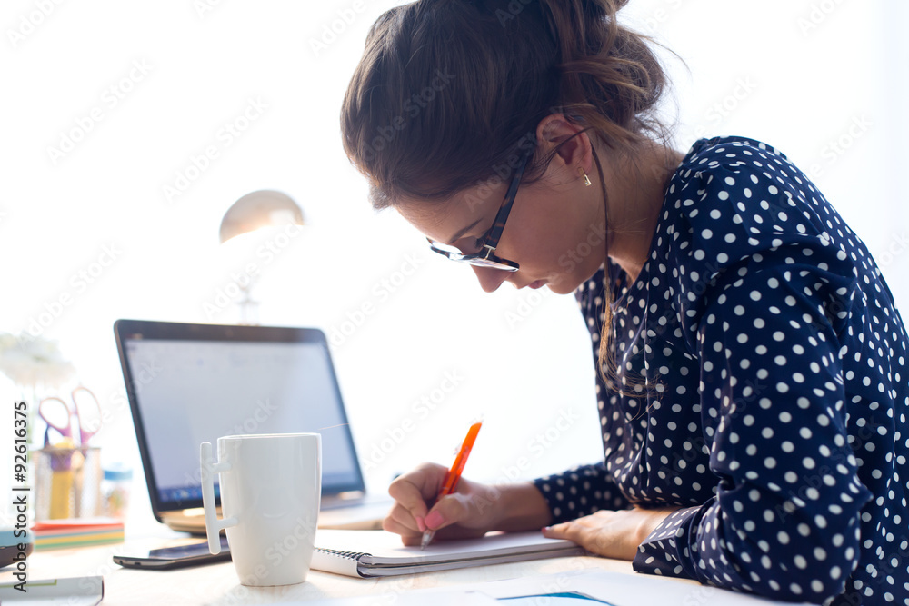 Fototapeta Beautiful young woman working in her office.
