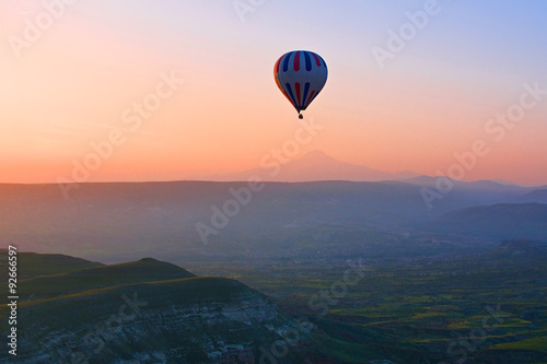 Fotografia, Obraz  Hot air balloon flying over amazing landscape at sunrise, Cappad