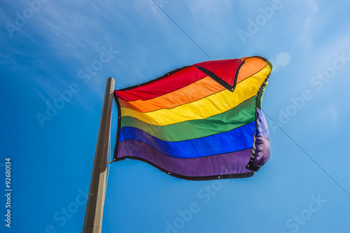Fotografía  Gay rainbow flag waving over blue sky background