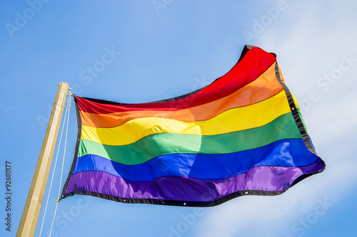 Pinturas sobre lienzo  Gay rainbow flag waving over blue sky background