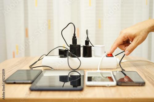 Fotografía  El hombre está apagando adaptadores de corriente para teléfonos móviles y tablet