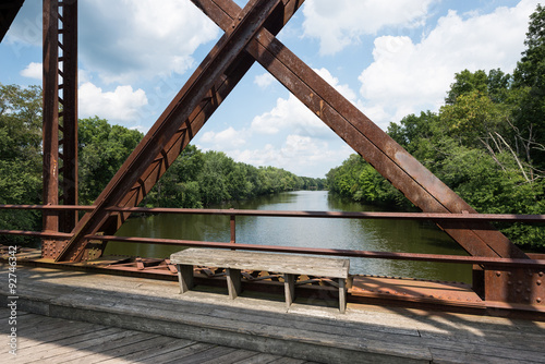 Fotografia, Obraz  Bench on the Wallkill River Rail Trail Bridge in Upstate New York with a view of the river through the bridge structure