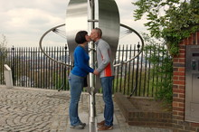 Man And Woman Kissing Being On Opposite Sides Of The Prime Meridian In Greenwich. London, UK.