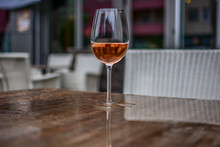Close-up Of A Glass Of Rose Wine On The Brown Table. Photographed On A Rainy Day. The Table Is Wet.