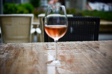 Glass Of Rose Wine On The Brown Table. Photographed On A Rainy Day. The Table Is Wet And Focus Is Behind Glass On Purpose.