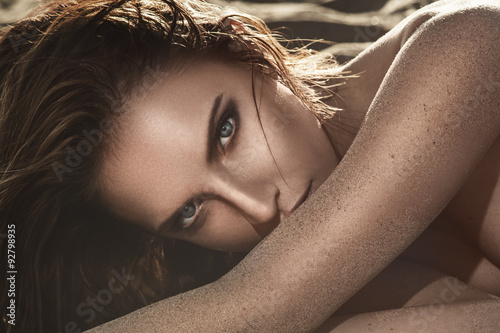 Beautiful woman lying on the sand Plakat