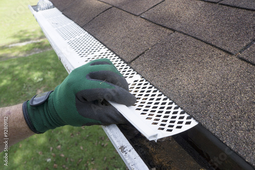 Photo Contractor Adjusting Plastic Gutter Guards