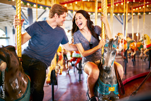 Fotografie, Obraz  romantic couple riding carousel together on date with blurred motion