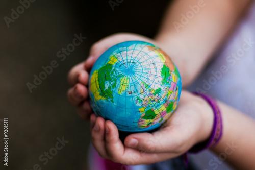 Fotografie, Obraz  Little girl holding the earth in her hands