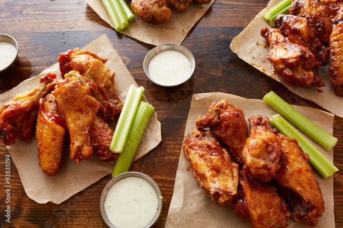Keuken foto achterwand Kip different flavored chicken wings with ranch dipping sauce and celery sticks on wooden table