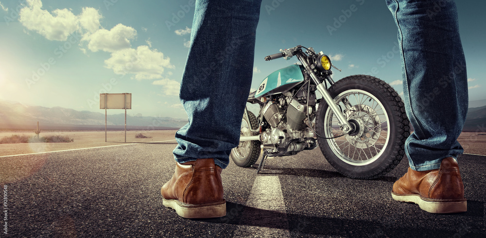 Fototapeta Sport. Biker standing near the motorcycle on an empty road at sunny day. Close view on legs