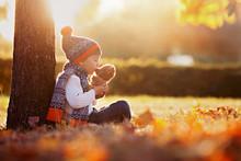 Adorable Little Boy With Teddy Bear In Park On Autumn Day