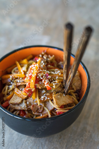 Fotografiet  Stir fry with vegetables and meat garnished with sesame seeds in bowl with chopsticks