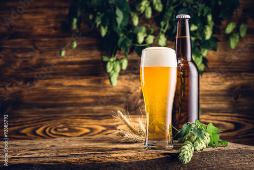 Glass of beer and bottle on old wooden table and wooden backgrou