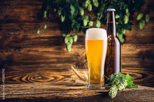 szklanka-piwa-i-butelka-na-starym-drewnianym-stole