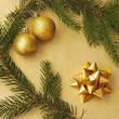 Christmas scenery - golden ribbon star decoration, two golden glass ball decorations and spruce tree branches on a golden background in the candle light.