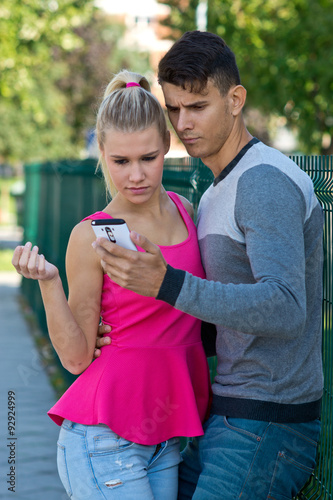 Keuken foto achterwand Ontspanning attractive couple with smartphone outside