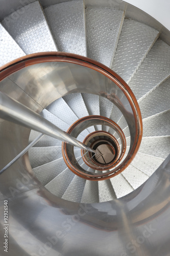 Tuinposter Trappen Metallic spiral stair with wooden handrails inside a lighthouse