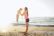family workout - mother and daughter doing exercises on beach. H