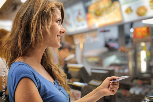 Young woman paying at a fast food restaurant Poster