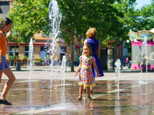 Two Sisters Playing With Fountain Splash