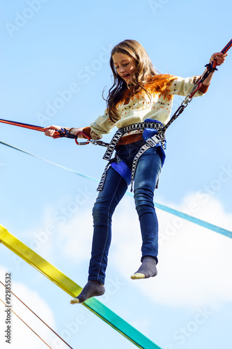 Fototapeta Teenage girl jumping with bungie
