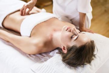 Obraz na płótnie Canvas Woman enjoys massage of tummy at the health spa