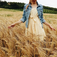 Low Section Of A Woman Standing In A Wheat Field