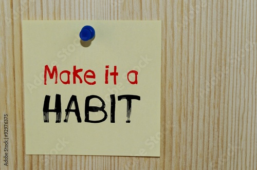 Fotografia  Make it a habit written on paper note over wooden background