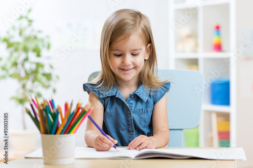 Valokuva  Portrait of lovely girl drawing with colorful pencils