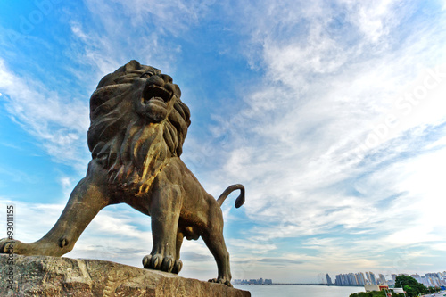 Fotografie, Tablou  Stone Lion sculpture, symbol of protection & power in Oriental Asia especially C