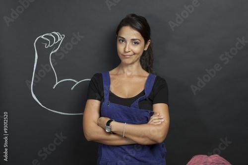 Bella ragazza indossa tuta da operaio con alle spalle braccio disegnato su lavagna