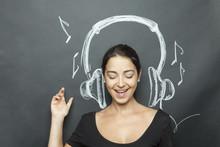 Giovane E Bella Ragazza Simula L'ascolto Di Un Brano Musicale Avendo Alle Spalle Delle Cuffie Disegnate Su Lavagna