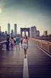 Smiling young woman tourist on Brooklyn Bridge