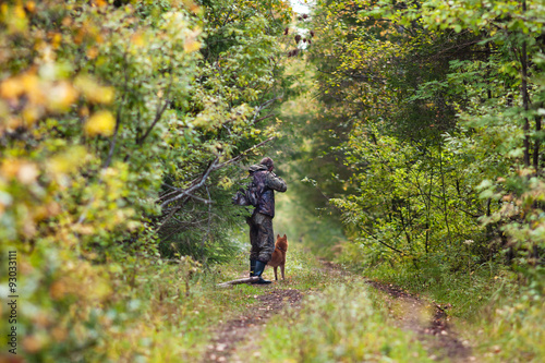 Foto op Aluminium Jacht hunter in camouflage with dog on forest road