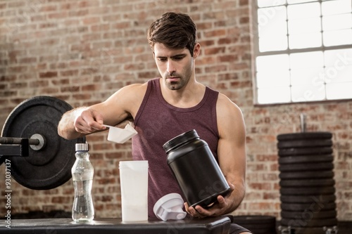 Fotografia  Man adding supplement from tin to bottle