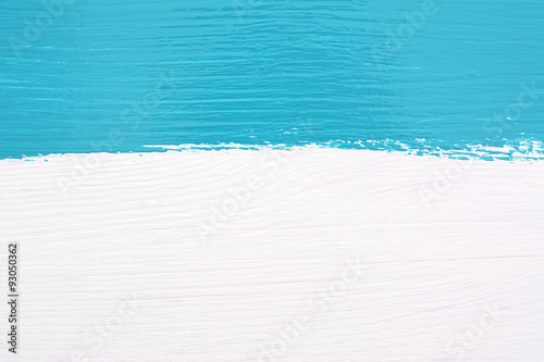 Stripe of teal paint over white wooden background
