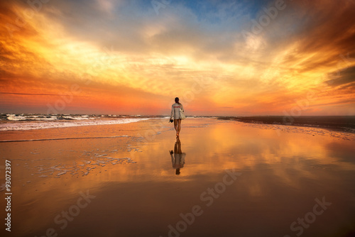 woman walking on the beach near the ocean at the sunset