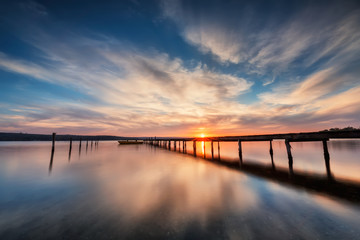 Fototapeta na wymiar Lake sunset. Magnificent long exposure lake sunset with boat and a wooden pier