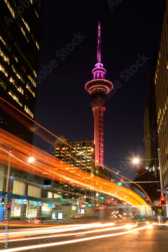 Motion traffic light trail of vehicles in Auckland CBD in the foreground with the Sky Tower in the background at dusk. Vertical