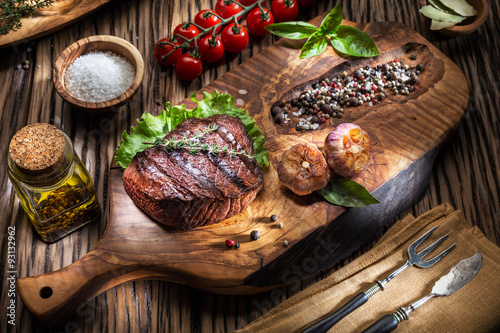 Foto auf Leinwand Grill / Barbecue Beef steaks with spices on a wooden tray.