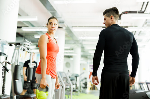 Photo  Young male trainer giving instructions to a woman in a gym