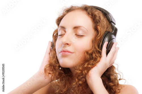 Fotografija  Beautiful curly girl listens to music through ear-phones