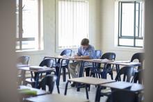 Schoolboy Writing In Classroom